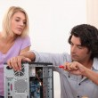 Man fixing computer with woman watching — Stock Photo