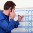 Man in blue overalls talking on the phone and writing on a board — Stock Photo