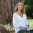 Young woman sat by tree with laptop — Stock Photo