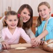 Mother rolling dough with two daughters — Stock Photo