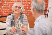 Older couple toasting at restaurant — Stock Photo