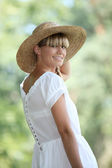 30 years old blonde woman wearing a white dress and a straw hat walking in — Stock Photo
