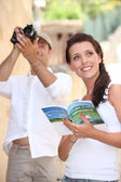 Tourists with camera and travel guide — Stok fotoğraf