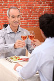 Senior man toasting with someone younger — Stock Photo