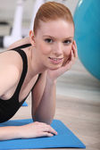Ginger haired woman laying of exercise mat in gym — Stock Photo