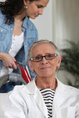 Young woman helping an older lady with the housework — Stock Photo