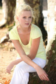 Platinum blonde woman near trees — Stock Photo