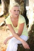 Platinum blonde woman near trees — Stock Photo