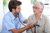 Medic listening to a senior woman's chest — Stock Photo