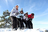 Four friends skiing together on holiday — Stock Photo