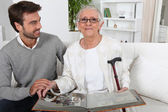 Elderly person looking at photos with son — Stock Photo
