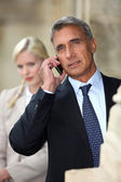 Businessman talking on cellphone outdoors — Stock Photo