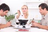 Three friends enjoying chocolate fondue — Stock Photo