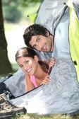 Jeune couple s'en tenir la tête hors de la porte de la tente — Photo
