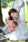 Young couple sticking their heads out of a tent door — Foto de Stock