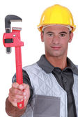 Man with a heavy duty adjustable pipe wrench — Stock Photo