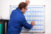 Construction worker writing in deadlines on a calender — Stock Photo