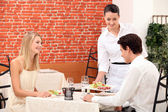 Waitress serving a young couple in a restaurant — Stockfoto