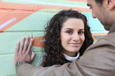 Flirtatious couple stood by wall — Stock Photo