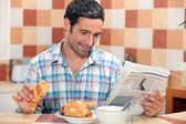 Man reading the newspaper while having breakfast — Stock Photo