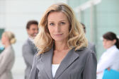 Woman standing in front of her colleagues — Stock Photo