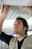 Man putting up a suspended ceiling — Stock Photo