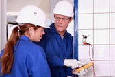 An electrician teaching how to use an ammeter — Stock Photo