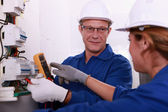 Electricians working on an electric meter — Stock Photo