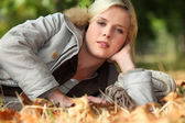 Woman lying on an autumnal forest floor — Stock Photo