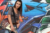 Attractive brunet singer with guitar against graffiti wall — Stock Photo