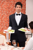 Waiter delivering meals to table — Stock Photo