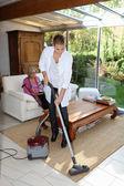 Young woman vacuuming — Stock Photo