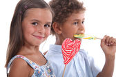 Two skittish kids with lollypops — Stock Photo