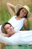 40 years old man and woman relaxing and lying down in a meadow — Stock Photo