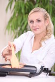 Woman sitting at a table using griddle — Stock Photo