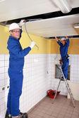 Dois eletricistas trabalhando no teto — Fotografia Stock