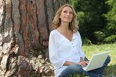 Jovem mulher sentou-se por árvore com laptop — Foto Stock