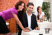 Woman leaning over a man in a restaurant with other diners in the backgroun — Stock Photo