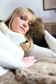Woman snuggling up on her sofa — Stock Photo