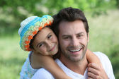 Daughter on Father's back — Stock Photo