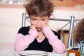 Sulky girl sitting at the breakfast table — Stock Photo