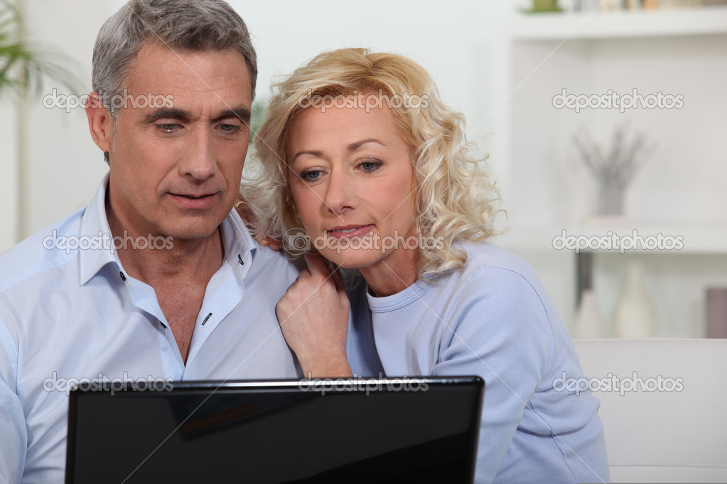 Couple looking at photos on their laptop — Stock Photo #8062871