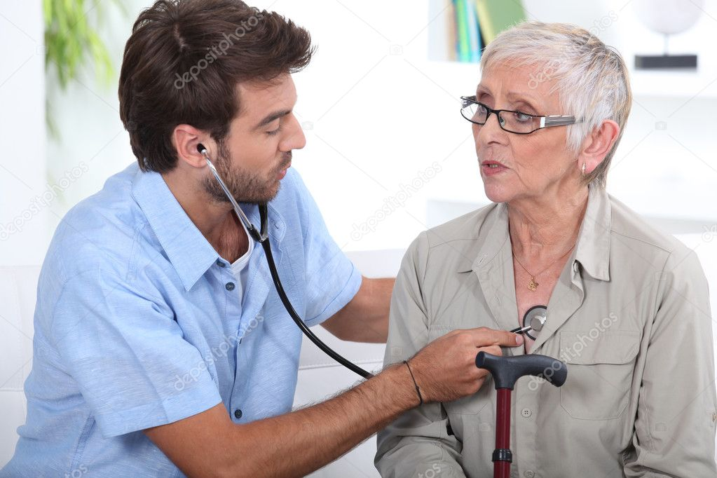 Medic listening to a senior woman's chest  Stock Photo #8062969