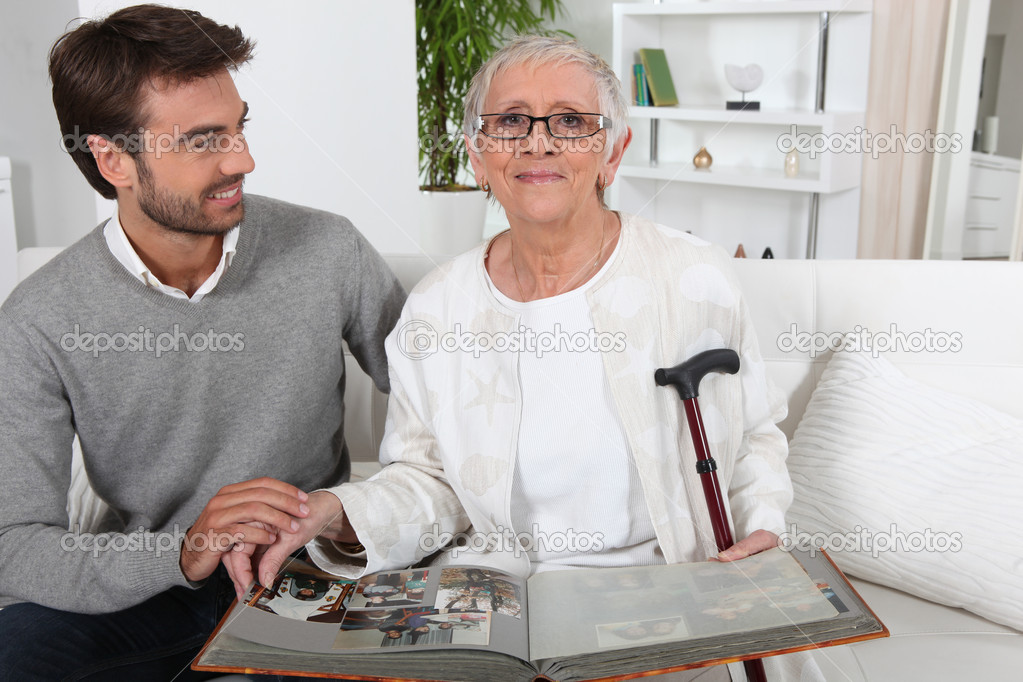 Elderly person looking at photos with son — Stock Photo #8063289
