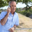 Grey-haired man making telephone call in park - Stock Photo