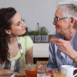 Elderly dame and young brunette having breakfast — Stock Photo