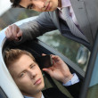 Two young businessmen sitting in a car and talking on a cell phone — Stock Photo