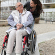 Stock Photo: Young wompushing elderly womin wheelchair