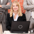 Young woman using laptop with collaborators — Stock Photo