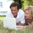Couple looking at their laptop in a park — Stock Photo